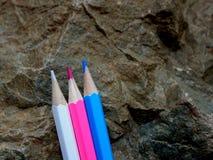 Trois crayons en pastel se penchant contre une roche images libres de droits