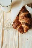 Trois croissants avec du chocolat et le lait sur la table en bois Images stock