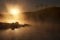 Trois croix au lever de soleil au-dessus d'un matin brumeux de Pâques de lac
