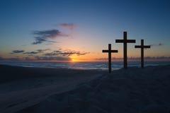 Trois croix sur la dune de sable à côté de l'océan avec un sunri nuageux images stock