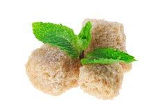 Trois cubes bruns en sucre de canne de morceau avec la menthe poivrée Images stock