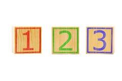 Trois cubes en bois bruns ont aligné dans une rangée avec des numéros un, deux Images stock
