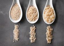 Trois cuillères en céramique avec les grains blancs organiques de quinoa images stock
