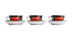 Trois cuvettes de thé noir avec des soucoupes d'isolement Photographie stock