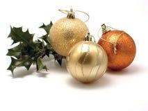 Trois décorations et houx de Noël Photos stock