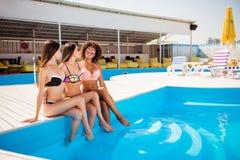 Trois dames chaudes, posant dans l'usage de natation et les lunettes, cuddli Photographie stock