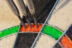Trois dards dans le secteur du triple vingt de la cible de sisal photographie stock
