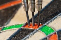 Trois dards dans le secteur triple de la cible de sisal image stock
