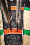 Trois dards frappant le score 180 parfait sur le panneau de dard Photographie stock