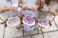 Trois demoiselles d'honneur tenant des paniers avec des pétales de rose Photos stock