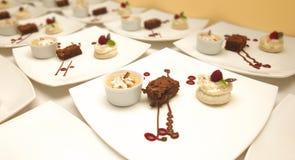 Trois desserts décorés différents ont servi dans des plats carrés en céramique blancs Images stock