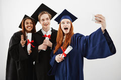 Trois diplômés heureux gais dupant avoir autour l'amusement souriant faisant le selfie au-dessus du fond blanc avec des diplômes  Photos libres de droits