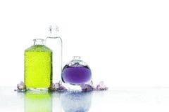 Trois diverses bouteilles avec le liquide et les fleurs de couleur Photographie stock