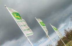 Trois drapeaux de John Deere volant sur des poteaux Photographie stock