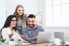 Trois employés enthousiastes recevant de bonnes nouvelles sur l'ordinateur portable image stock