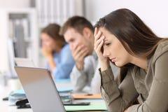 Trois employés inquiétés lisant la mauvaise nouvelle sur la ligne photos libres de droits