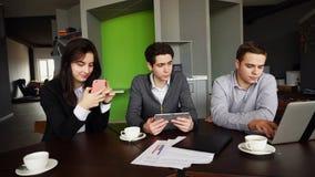Trois employés occupés de société, deux jeunes hommes et femme occupés avec images stock