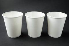 Trois emportent des tasses de livre blanc pour le caf? chaud, le th?, le jus et d'autres boissons d'isolement sur le noir Pr?sent photographie stock libre de droits