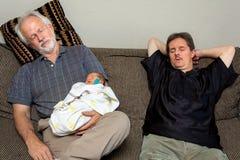 Trois endormis sur un grand-père et un homme nouveau-nés de bébé de divan avec font photo stock