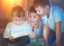 Trois enfants à l'aide de la tablette dans une chambre noire Images libres de droits