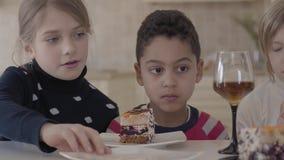 Trois enfants à la table avec de petits verres de gâteau et de jus La main d'une femme coupe le gâteau et met un morceau au pl banque de vidéos