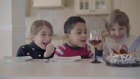 Trois enfants à la table avec de petits verres de gâteau et de jus La main d'une femme coupe le gâteau pour des enfants Caucas banque de vidéos