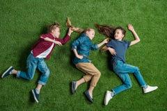 Trois enfants adorables se trouvant ensemble sur la pelouse verte Photos stock