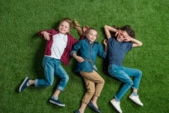 Trois enfants adorables se trouvant ensemble sur la pelouse verte Photo libre de droits