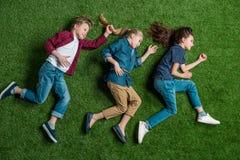 Trois enfants adorables se trouvant ensemble sur la pelouse verte Image libre de droits