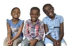 Trois enfants africains tenant dessus un autre sourire Photo stock
