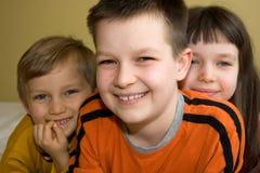 Trois enfants avec des sourires de lancement Images stock