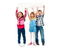 Trois enfants avec les bouches ouvertes tenant la feuille de papier vide Photos stock