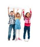 Trois enfants avec les bouches ouvertes tenant la feuille de papier vide Photo stock