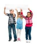 Trois enfants avec les bouches ouvertes tenant la feuille de papier vide Photographie stock