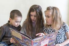 Trois enfants ayant l'amusement lisant un livre Deux soeurs et un frère Fond clair Aspect européen Photos libres de droits