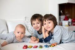 Trois enfants, bébé et ses frères plus âgés dans le lit dans le mornin Photographie stock libre de droits