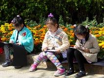Trois enfants chinois dessinant au parc de siècle Image stock