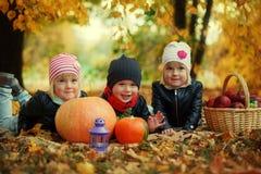Trois enfants d'amis se trouvant sur des feuilles d'automne avec les potirons et la pomme Photographie stock libre de droits