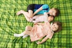 Trois enfants d'enfant de mêmes parents se trouvant sur le lit dans la famille nombreuse Photo stock