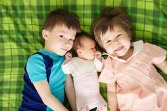 Trois enfants d'enfant de mêmes parents se trouvant sur le lit dans la famille nombreuse Images libres de droits