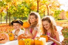 Trois enfants dans des costumes ouvrant des potirons de Halloween Photos stock