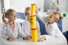 Trois enfants dans des manteaux de port de laboratoire de laboratoire de science photo stock