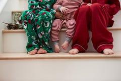 Trois enfants dans des pyjamas se reposant sur des escaliers à Noël Image stock