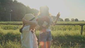 Trois enfants de filles avec le bouquet du doigt d'exposition de fleurs sur la route, les émotions joie et le bonheur, attendent  clips vidéos
