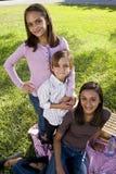 Trois enfants de mêmes parents ayant le pique-nique dans le stationnement Photo stock