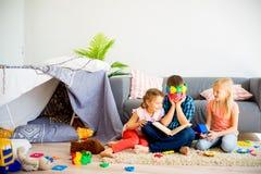 Trois enfants de mêmes parents lisant un livre Image stock