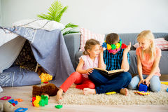 Trois enfants de mêmes parents lisant un livre Photographie stock libre de droits
