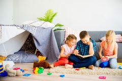 Trois enfants de mêmes parents lisant un livre Photos libres de droits