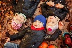 Trois enfants de sourire d'amis se situant dans des feuilles d'automne Image stock