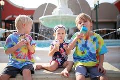 Trois enfants en bas âge mangeant la crème glacée par la fontaine le jour d'été Images libres de droits